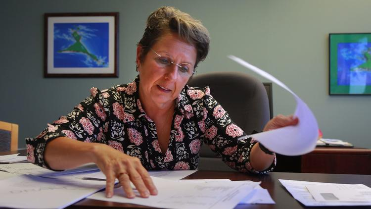 Lisa Fine, executive director of San Diegos's Parkinson's Association, uses a draft audit to explain the financial troubles that have forced the organization to temporarily suspend most of its programs. (Peggy Peattie, San Diego Union-Tribune)